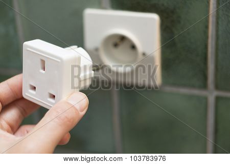 Close Up Of Hand Putting Electric Travel Adapter Into European Socket
