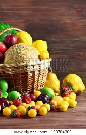 Assorted of fresh fruits in wicker baskets on wooden background