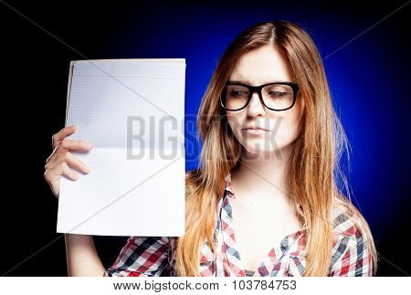 Disappointed Young Girl With Nerd Glasses Holding Open Exercise Book