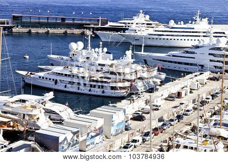 Super yachts sailing boats and ships docked in Monte Carlo Monaco harbor by a pier with parked cars