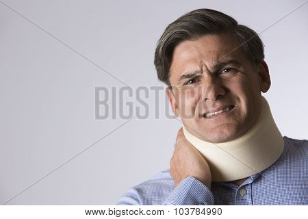 Studio Shot Of Man In Pain Wearing Neck Brace
