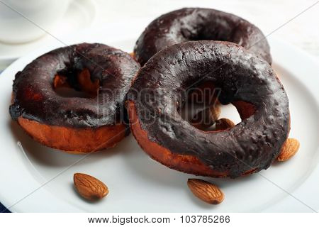 Delicious doughnuts with chocolate icing and nuts on plate close up