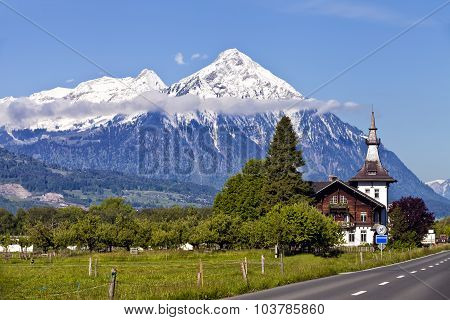 Swiss Alps landscape with snow mountain peaks green fields wooden traditional house by a road on a s