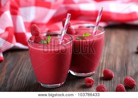 Glasses of raspberry milk shake with berries on wooden table close up