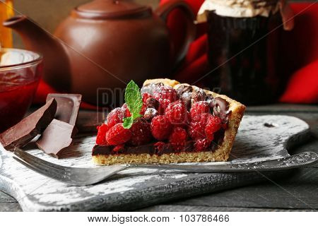 Piece of tart with fresh raspberries, on wooden background