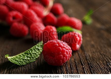 Fresh red raspberries on wooden table, closeup