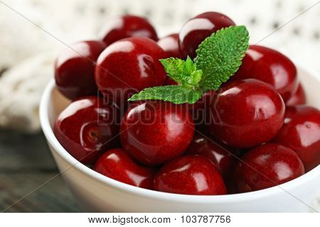 Sweet cherries with green leaves in bowl, on wooden background