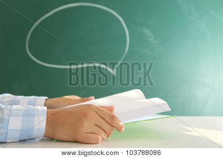 Women hands with book on blackboard background