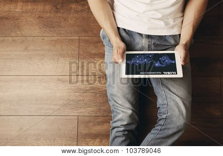Young man sitting on floor with tablet in room