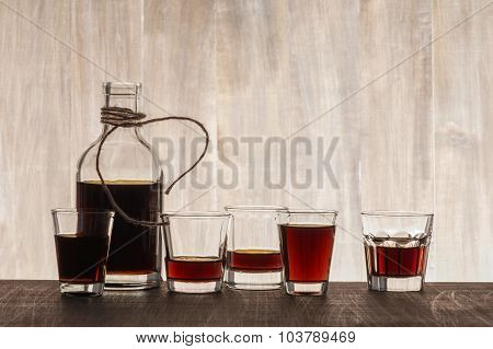 Glass Bottle And Shots On The Wooden Background