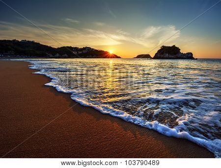 Rolling waves against the smooth sand and sunset peaking through the hill