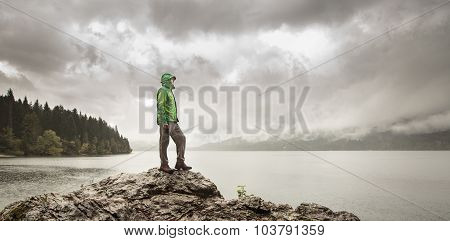 Man Standing On A Rock Beside A Mountain Lake In Rain