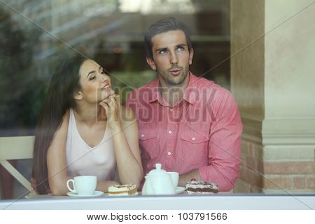 Young couple drinking tea and talking in cafe