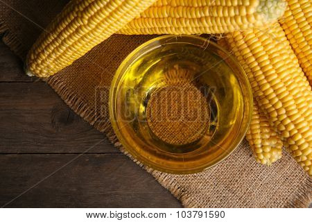 Fresh corn with bowl of oil on table close up