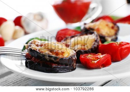 Dish of eggplant with cherry tomatoes and cheese in white plate on wooden table, closeup