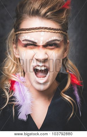 American Indian warrior with paint face camouflage, screaming with mouth open - studio photo with professional makeup