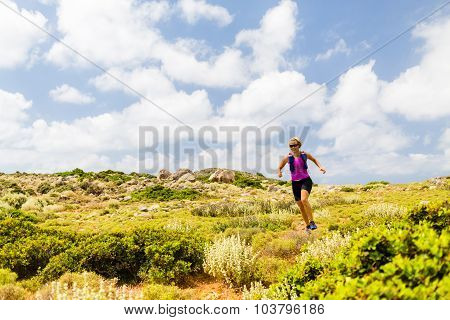 Trail running woman cross country running in inspirational mountain landscape on beautiful day. Trai