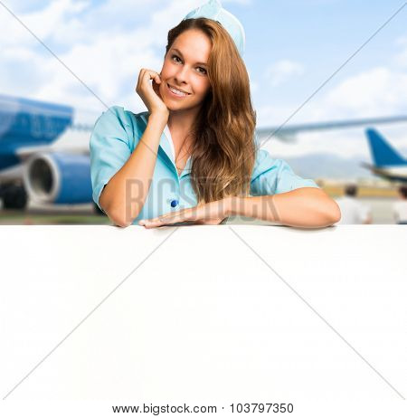 Portrait of a smiling stewardess showing a blank panel