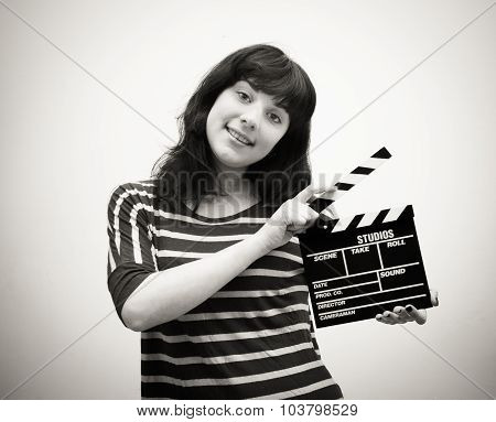 Young Woman Smiling With Movie Clapper Board