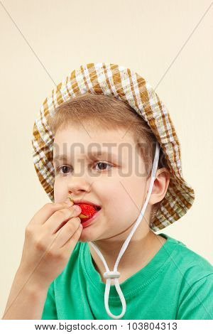 Little boy in the summer hat eating fresh ripe strawberry