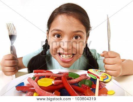 Happy Excited Latin Female Child Holding Fork And Knife Sitting At Table Ready For Eat A Dish Full O