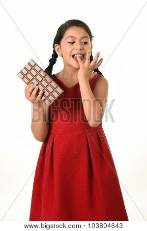Hispanic Female Girl Wearing Red Dress Holding Big Chocolate Bar Eating In Happy Excited Face Expres