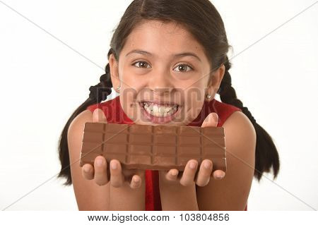 Latin Female Child Holding With Both Hands Big Chocolate Bar In Front Of Her Happy Smiling Face