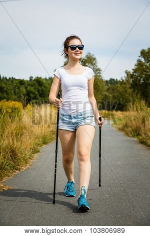 Nordic walking - young woman working out in park