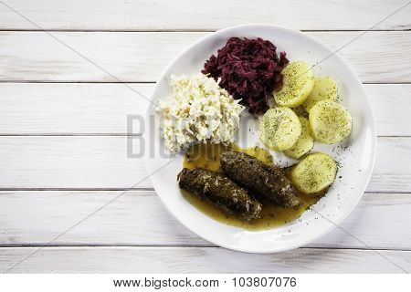 Wrapped stuffed beef, boiled potatoes and vegetables