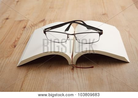Blank Notepad with spectacles on Wooden Table.