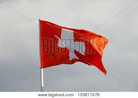 Swiss flag waving against blue sky
