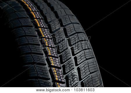 Winter tire closeup, dark backgroud