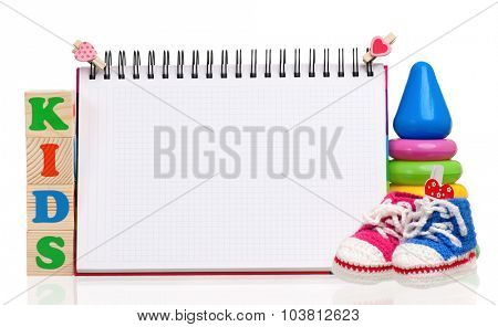 Kids words formed by wood alphabet blocks and blank notepad for text, isolated on white background