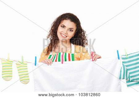 Young housewife hanging clothes on the line, isolated on white background
