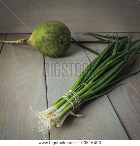 Green onions and radishes on a wooden background