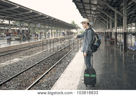 Train Delay. Young Asian Man Looking In His Watch While Waiting Train At Station