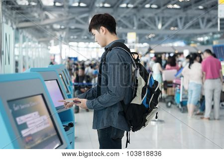 Young Asian Man Using Self Check-in Kiosks In Airport