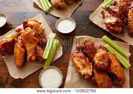 different flavored chicken wings with ranch dipping sauce and celery sticks on wooden table