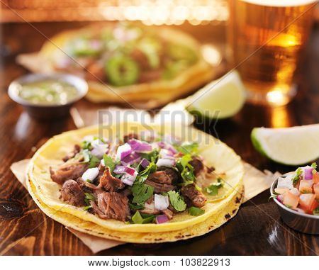 two mexican street tacos with barbacoa beef served on yellow corn tortilla with beer in background