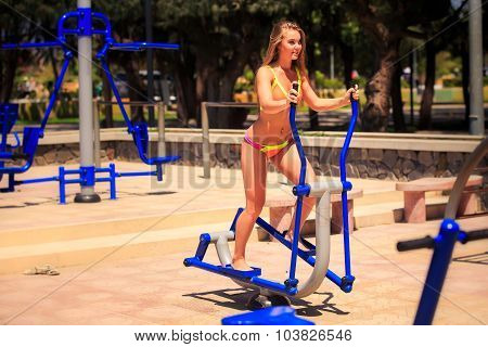 Blonde Slim Girl In Bikini Stands On Stepper On Sports Ground