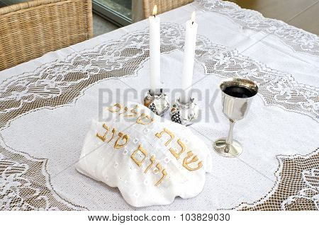 Shabbat eve table with covered challah bread candles and cup of wine.