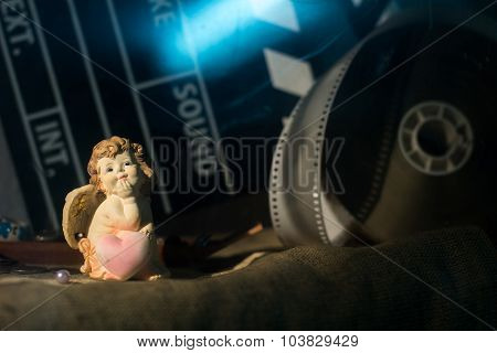 Figurine Little Angel With A Heart Who Dreams Against The Backdrop Of A Movie Clip And Firecrackers