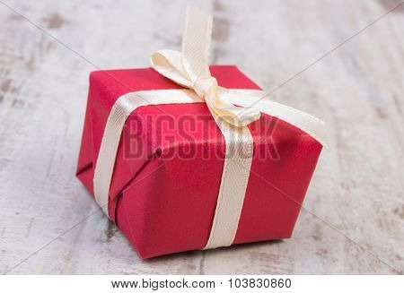 Red Gift For Christmas Or Other Celebration On Wooden Plank