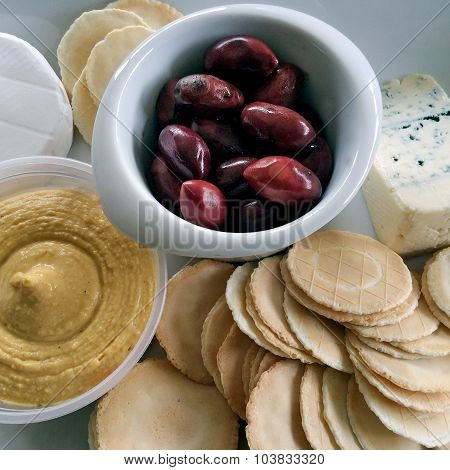 Kalamata olives served as appetisers with blue vein cheese crackers and hummus.