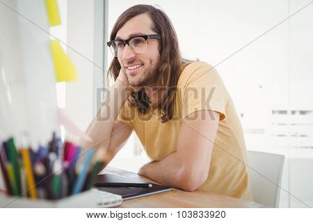 Hipster wearing eye glasses working at computer desk in office