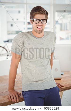 Portrait of happy hipster wearing eye glasses leaning at desk in office