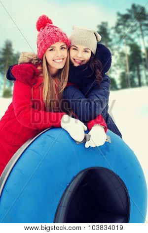 winter, leisure, sport, friendship and people concept - happy girl friends with snow tubes hugging outdoors