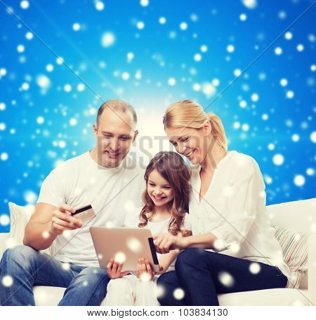 family, christmas holidays, shopping, technology and people - smiling family with tablet pc computer and credit card over blue snowy background