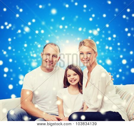 family, childhood, christmas holidays and people - smiling mother, father and little girl over blue snowy background