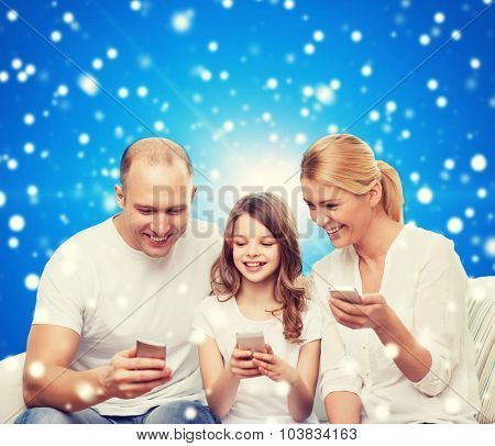 family, christmas holidays, technology and people - smiling mother, father and little girl with smartphones over blue snowy background